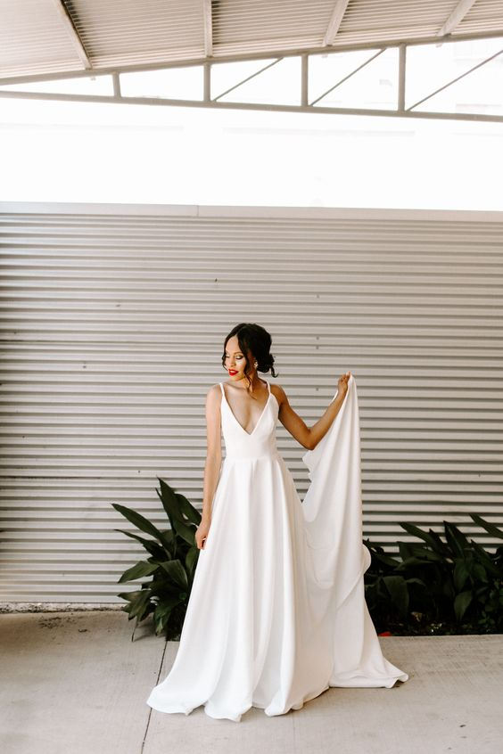 a sexy wedding ballgown with a plunging neckline, spaghetti straps and a draped skirt plus a train