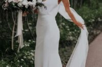 a sheath slip plain wedding dress and a veil for a chic minimalist bridal look