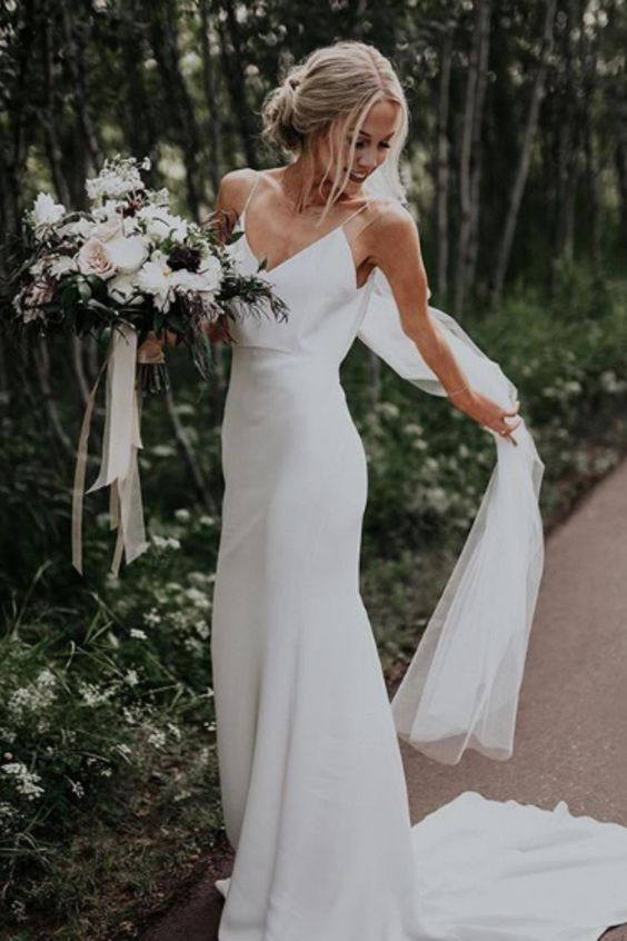a sheath slip plain wedding dress and a veil for a chic minimalist bridal look