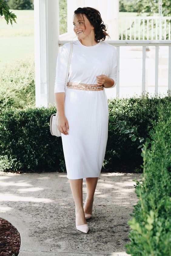 a simple and stylish white plain midi dress with a high neckline, short sleeves, an embellished waistline and blush shoes
