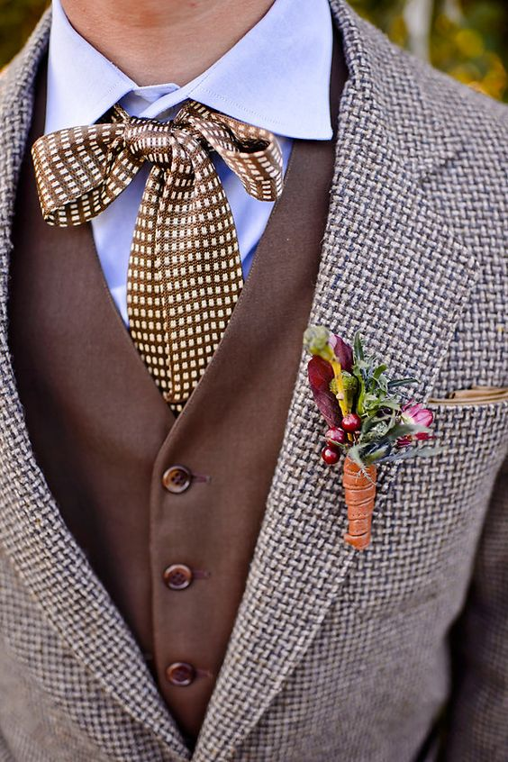 a stylish tweed suit, a brown waistcoat, a blue shirt, a printed bow plus a berry and flower boutonniere