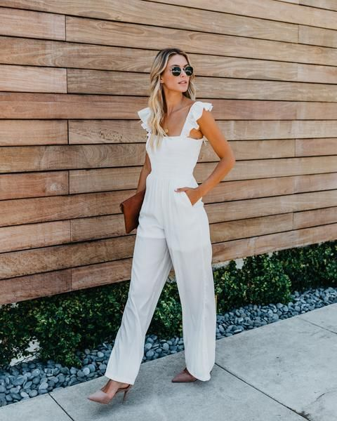 a stylish white jumpsuit on ruffle straps, dusty pink shoes and a brown clutch for a simple and chic look