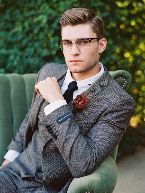 a vintage groom's outfit with a grey tweed three-piece suit, a white shirt, a black tie and stylish glasses
