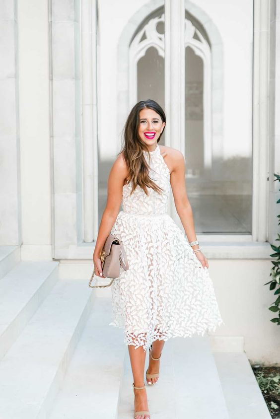 a white lace A-line midi dress with a halter neckline, nude shoes and a neutral bag