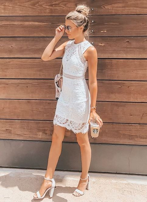 a white lace sheath mini dress with a halter neckline, white block heels and a blush bag