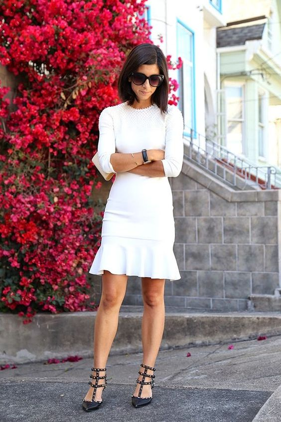 a white long sleeve dress with a high neckline and a texture, a pleated skirt, black sutdded shoes for a modern bride-to-be