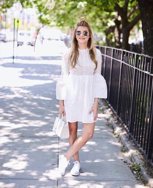 a white mini dress with a lace bodice, a plain skirt, bell sleeves of lace and plain fabric, white sneakers and a bag