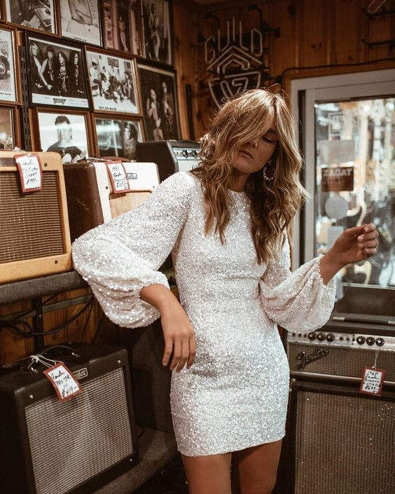 a white sequin mini dress with a high neckline, puff sleeves and statement earrings for a fun-loving bride
