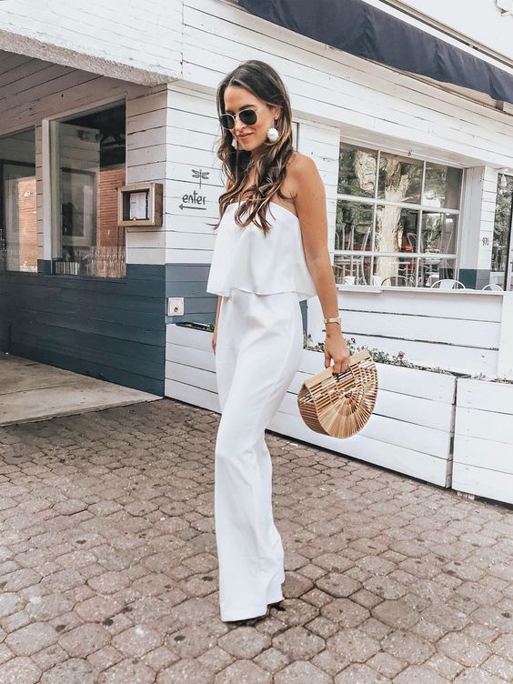 a white strapless jumpsuit with a tiered bodice, statement earrings and a wooden bag