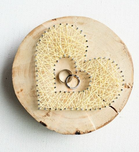 a wood slice with nail and yarn hearts is a trendy and bold idea for a woodland or rustic wedding