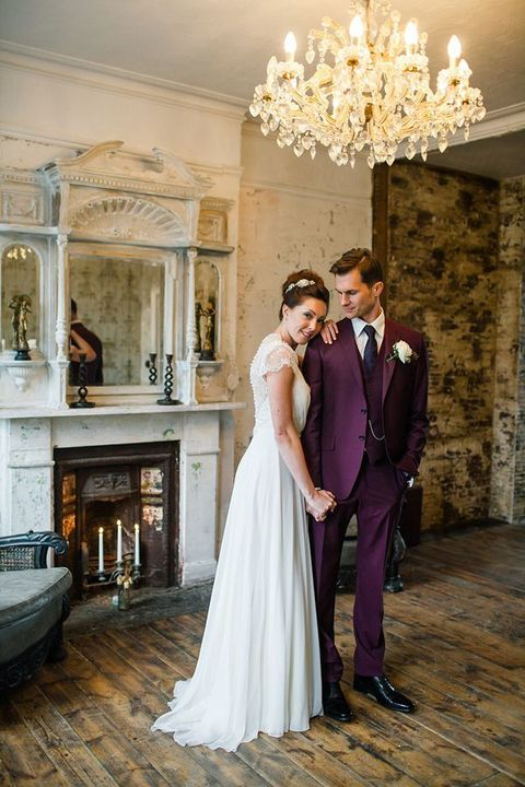 an elegant vintage-inspired groom's outfit with a burgundy three-piece suit, a black tie and shoes plus an off-white button down