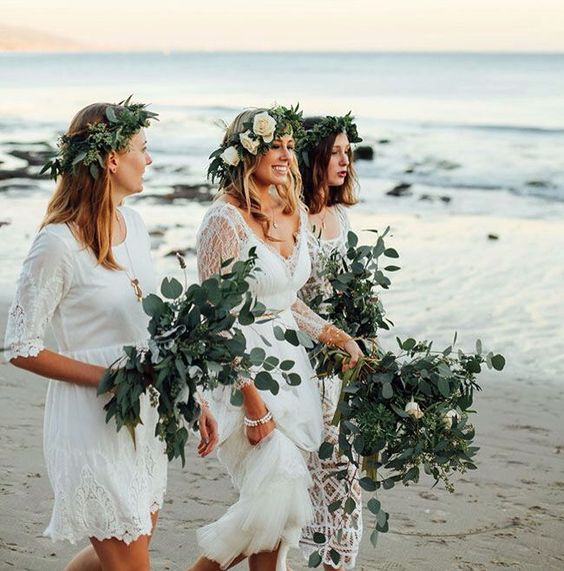 mismatched white lace dresses with a boho feel and greenery crowns for a boho beach wedding