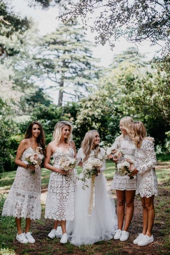 mismatching white boho lace mini and midi bridesmaid dresses and white sneakers for maximal comfort at the wedding