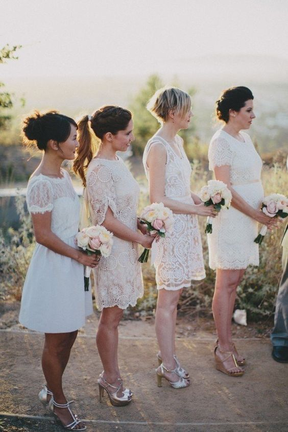 mismatching white lace over the knee bridesmaid dresses and silver shoes for a spring or summer elegant weddin