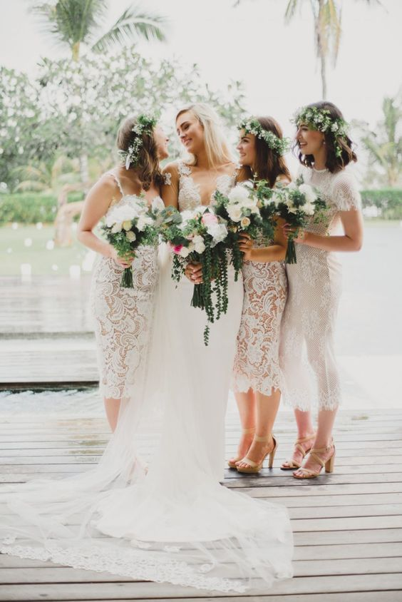 stylish white lace fitting midi bridesmaid dresses with mismatching necklines and nude shoes for a spring or summer wedding