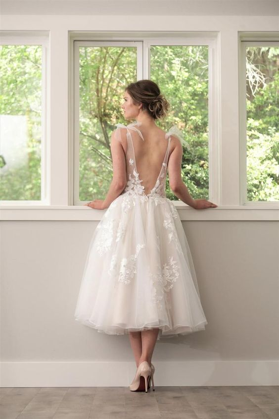 a beautiful A-line tea length wedding dress with lace appliques, an open back, nude shoes for a refined look