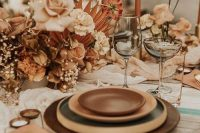 a beautiful boho wedding tablescape with brown and amber plates, gold and copper cutlery and blush and rust blooms