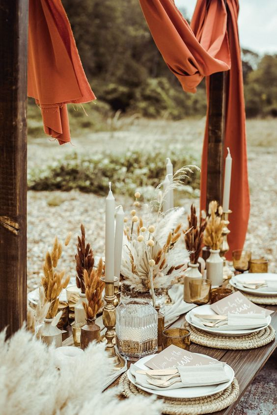 a beautiful boho wedding tablescape with woven placemats, grasses in vases, candles and rust fabric over the table