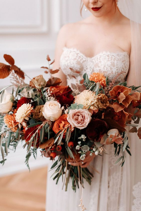 a beautiful burgundy, rust, orange, blush flower wedding bouquet with greenery for a fall bride