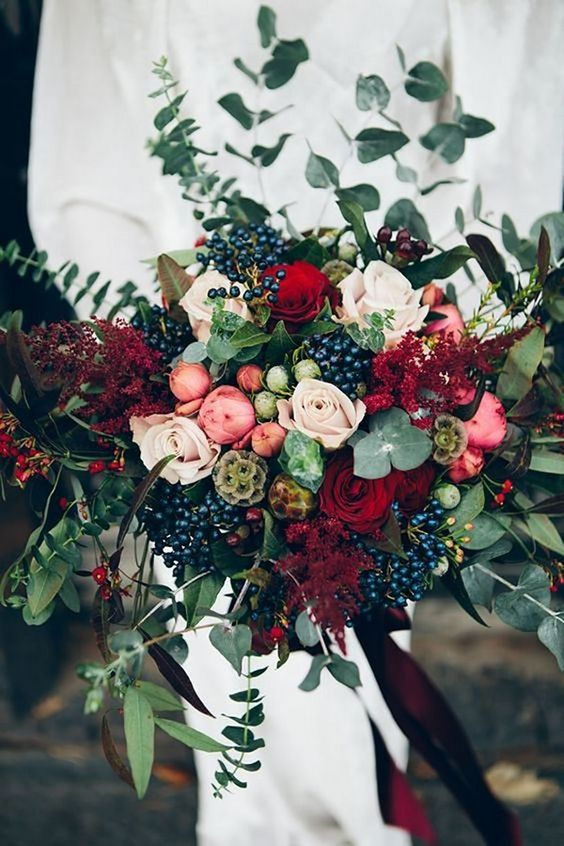 a beautiful dimensional fall wedding bouquet with berries, greenery, blush and pink blooms and touches of deep red