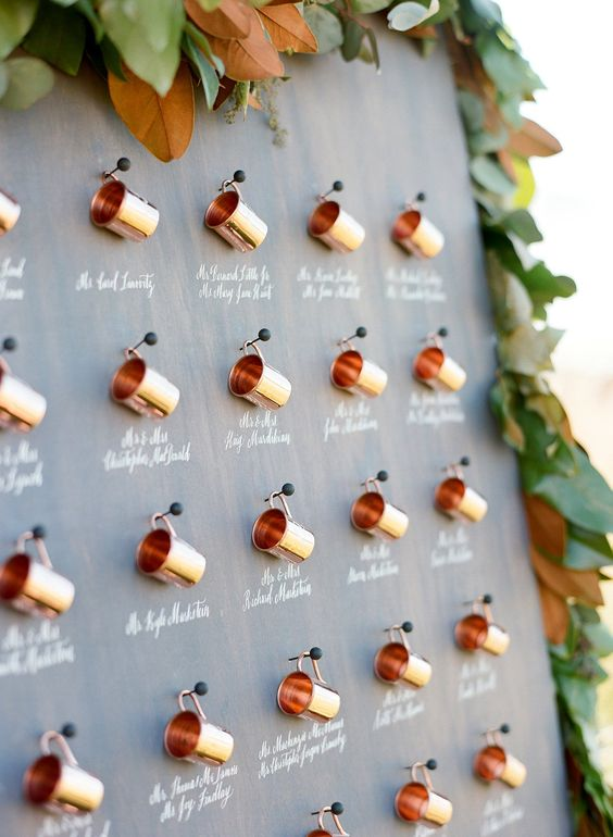 a beautiful fall seating chart of mini copper mugs on pins decorated with lush greenery and magnolia leaves