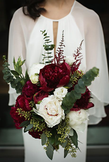 a beautiful fall wedding bouquet of burgundy and white blooms and greenery