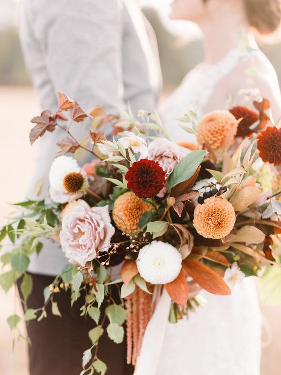 a beautiful fall wedding bouquet of white, pink, burgundy, orange blooms, greenery and dark foliage with much dimension is amazing
