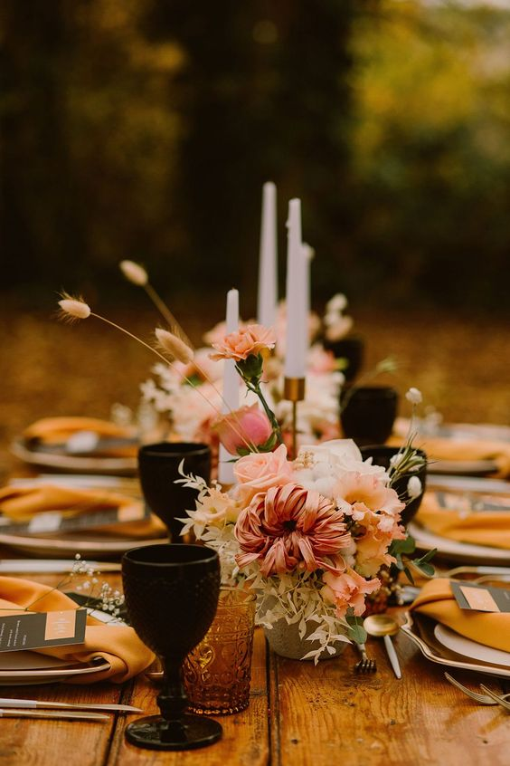 a beautiful fall wedding tablescape with pink blooms and greenery, black and amber glasses, tall candles and mustard napkins