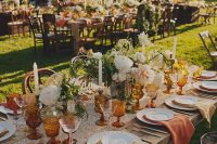 a beautiful wedding tablescape with rust and amber napkins, a floral runner, neutral blooms and greenery and amber glasses