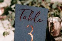 a black and copper table number paired with a lush greenery centerpiece for a modern fall tablescape