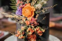 a black wedding cake decorated with fresh bold fall bloos and greenery and leaves