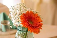 a blue jar with baby's breath and a bright dahlia plus a table number and candles make up a nice rustic centerpiece