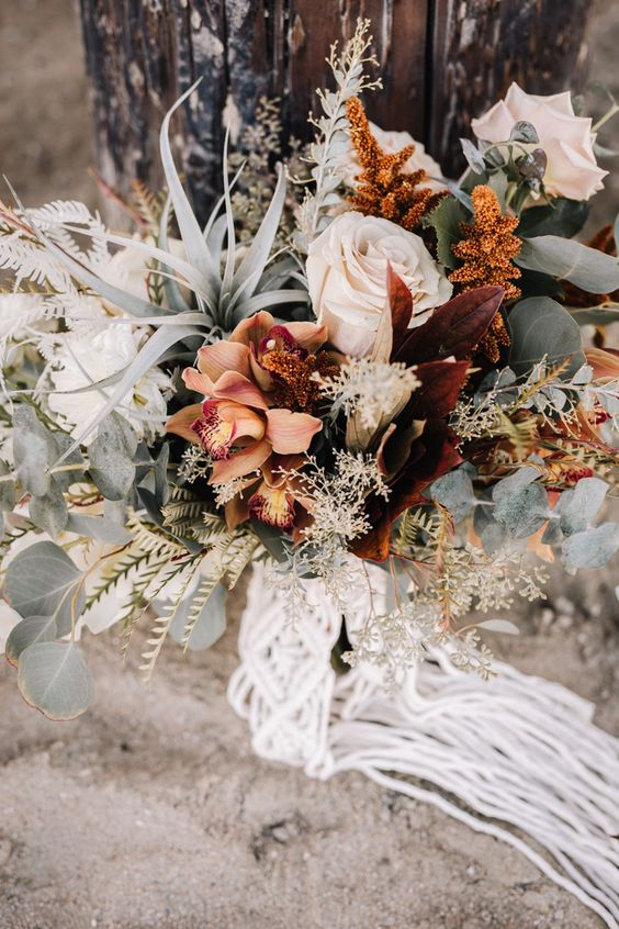 a boho fall wedding bouquet of rust, blush blooms, dark foliage and greeneyr, air plants, grasses and macrame with fringe is amazing