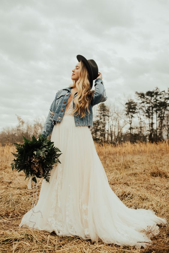 a boho lace A-line wedding dress with a train, a blue denim jacket, a black hat for a boho elopement
