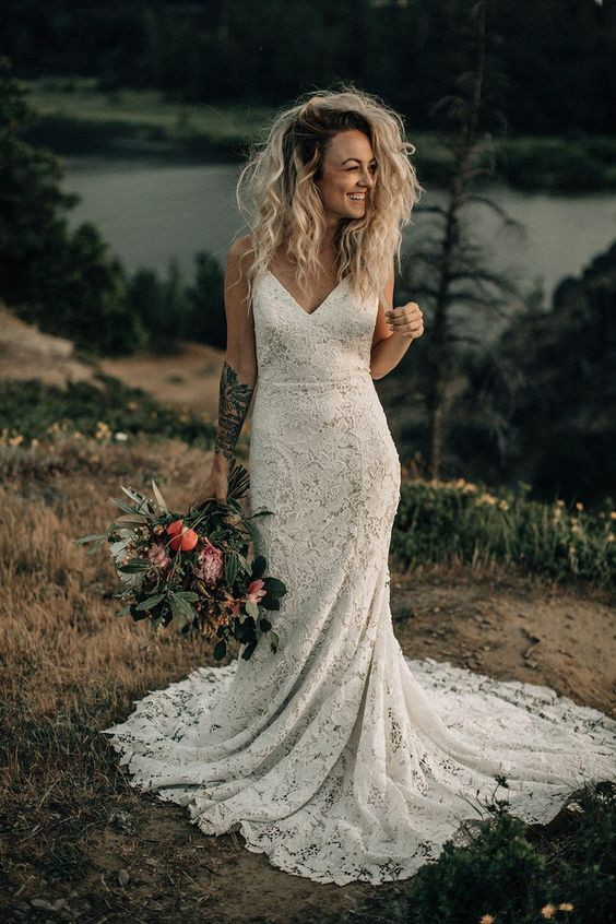 a boho lace fitting wedding dress on spaghetti straps and a train for a boho elopement