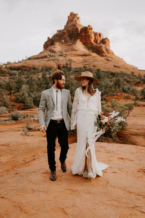 a boho lace fitting wedding gown with long sleeves and a front slirt plus a small train and a hat for a boho elopement