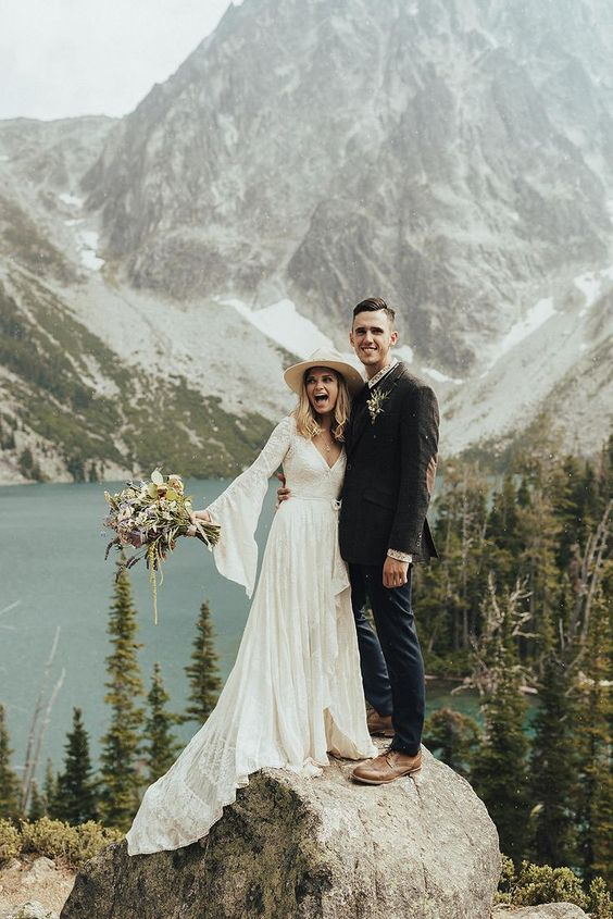 a boho lace high low wrap wedding dress with bell sleeves and a train for a mountain and lake elopement with a wild feel
