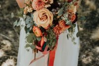 a bold and catchy wedding bouquet of rust, yellow, deep purple blooms, berries and seeded eucalyptus plus bright ribbons