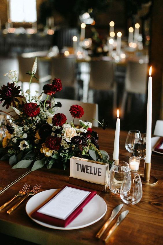 a bold and chic fall wedding centerpiece with burgundy, purple and white blooms and greenery and white candles