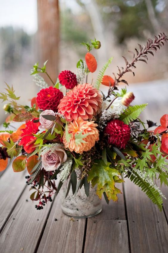 a bold and textural wedding centerpiece of red, mauve, rust and blush blooms, greenery, foliage for a fall celebration