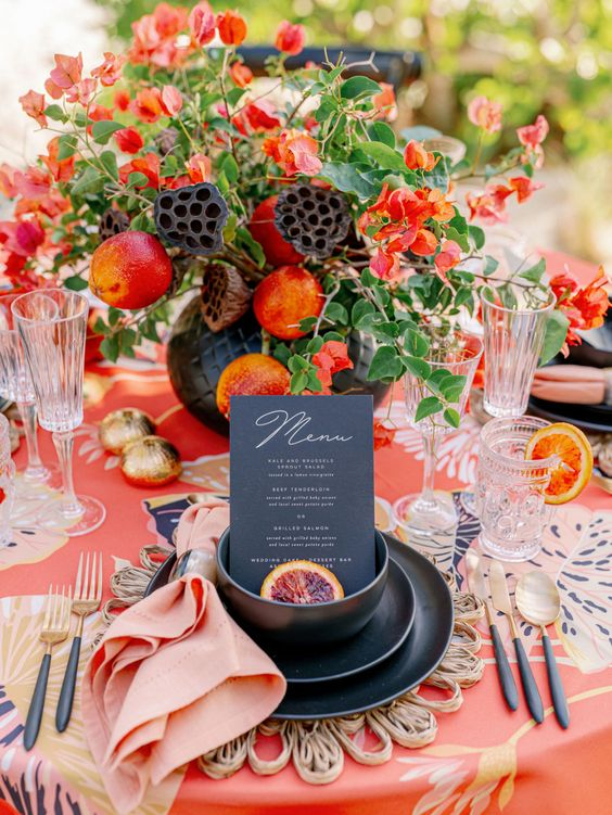 a bold fall wedding centerpiece of greenery, red blooms and fruits, some lotus blooms is lovely
