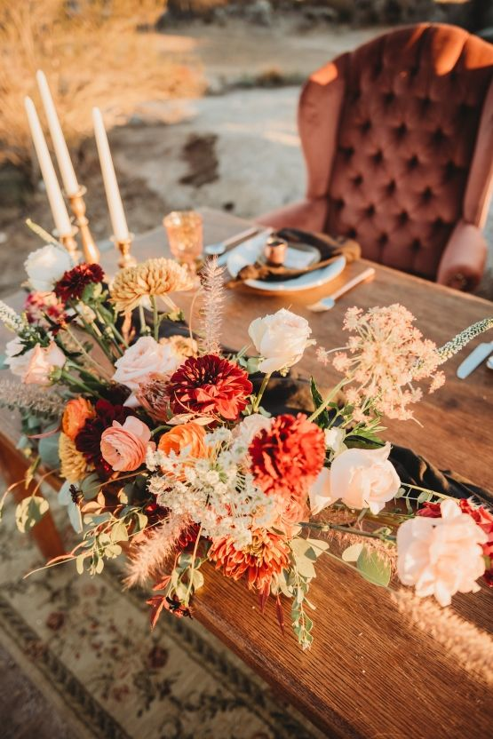 a bold fall wedding centerpiece of white, rust, orange and blush blooms, dried herbs and foliage