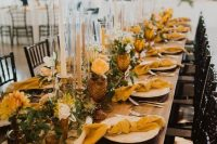 a bold fall wedding table setting with a neutral runner, candles and plates, yellow napkins, blooms and amber glasses