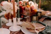 a bold fall wedding tablescape with a rust runner and grey napkins, matching candles, bold floral arrangements and gold cutlery is wow
