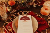 a bold fall wedding tablescape with rust, red, burgundy blooms, amber stone candleholers, a red napkin, amber cutlery and a placemat