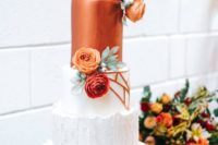 a bold geometric wedding cake in whte and copper and with bright blooms and foliage