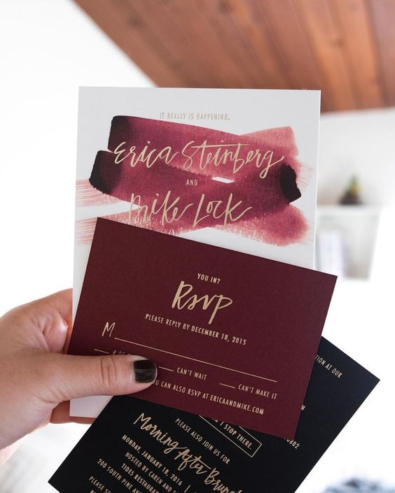 a bold invitation in black, burgundy and white, with ombre brushstrokes and gold calligraphy