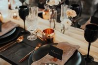 a bold modern wedding tablescape with copper cutlery and mugs, black glasses and plates plus dusty pink napkins