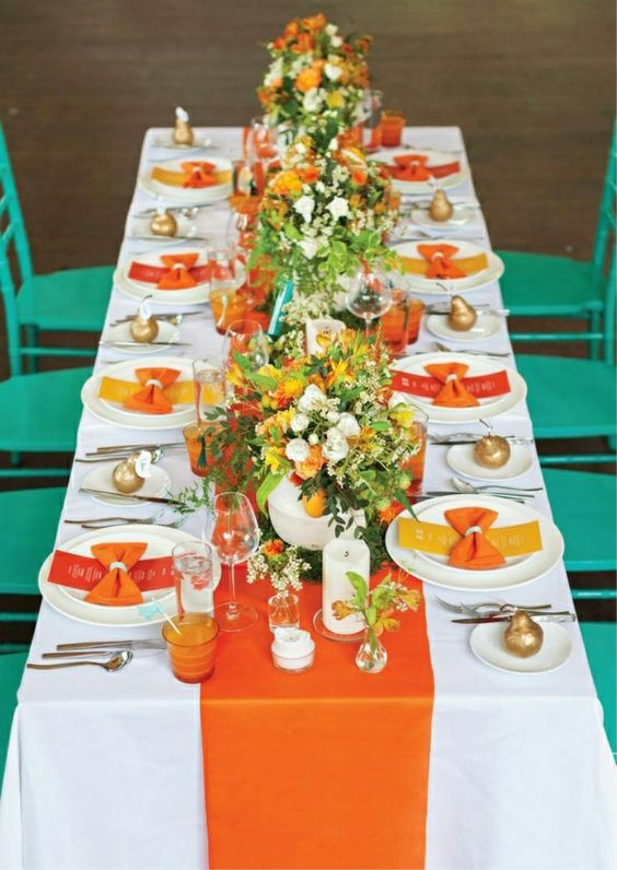 a bold orange fabric table runner and echoing glasses and menus for a bold autumn celebration