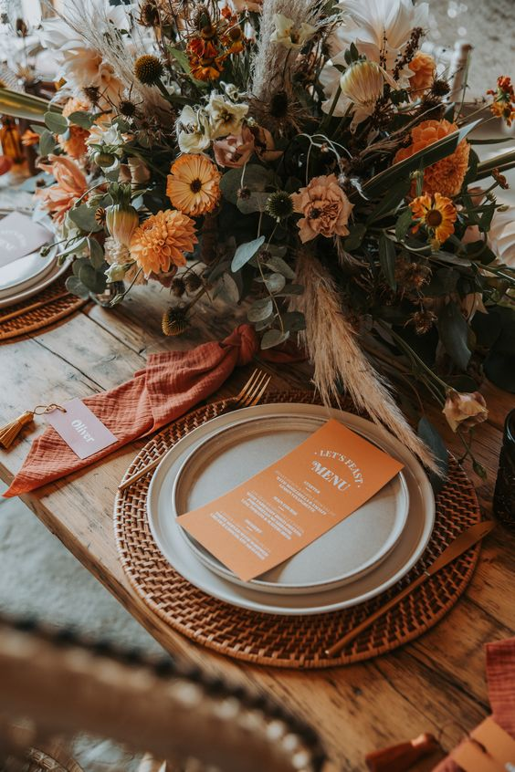 a bold retro inspired wedding tablescape with a woven placemat, neutral plates, orange napkins, a bold orange and neutral bloom centerpiece with greenery